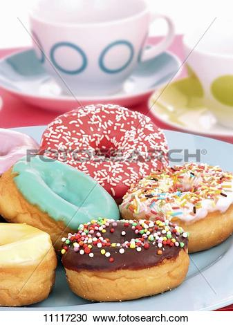 Stock Photography of Colourful glazed doughnuts on a plate.