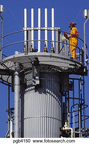 Stock Photography of Engineer checking distillation column in.