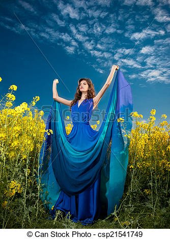 Stock Photo of Girl in blue dress in colza field.