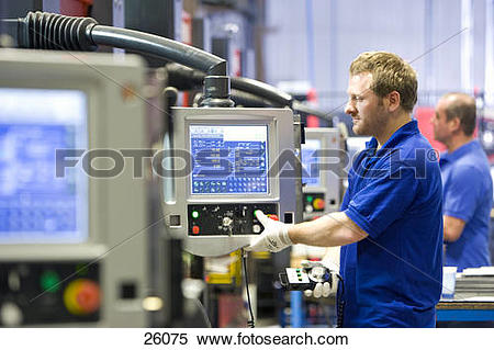 Stock Image of Worker operating computer controlled machinery in.