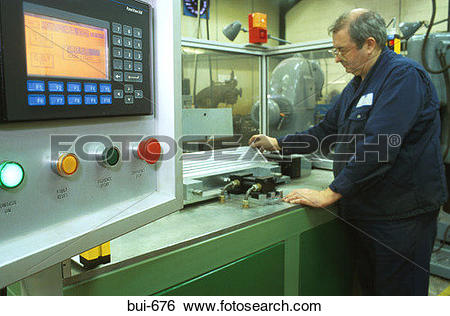 Stock Images of Man Using Computer Controlled Lathe in Factory bui.