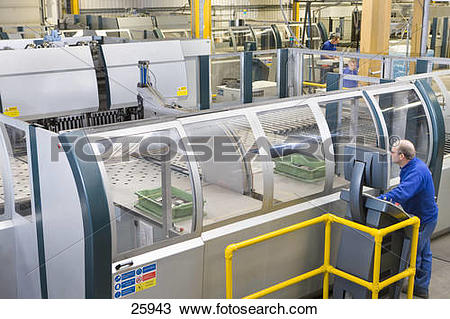 Stock Photo of Worker operating computer controlled machinery in.