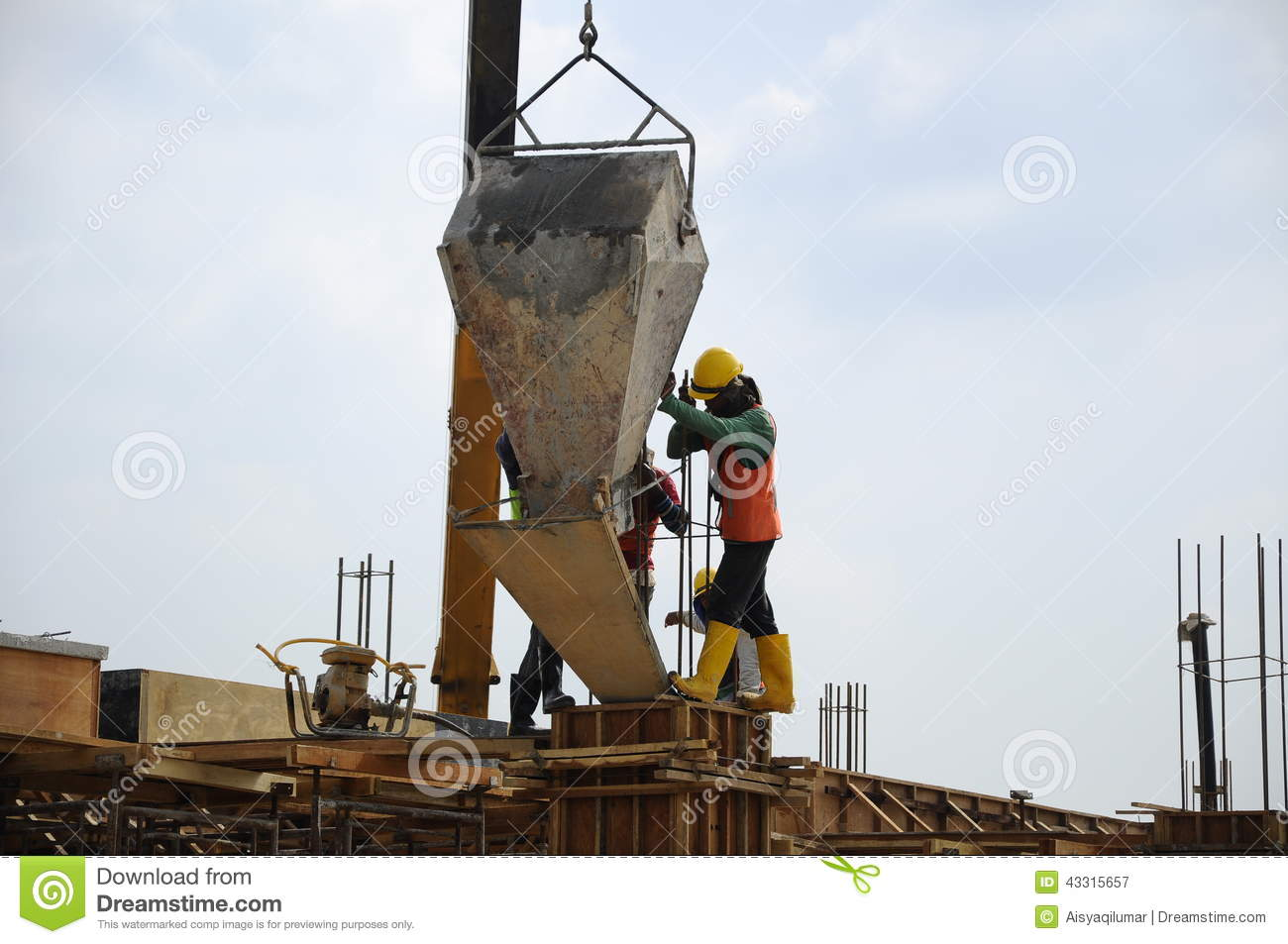 A Group Of Construction Workers Pouring Concrete Into Formwork.