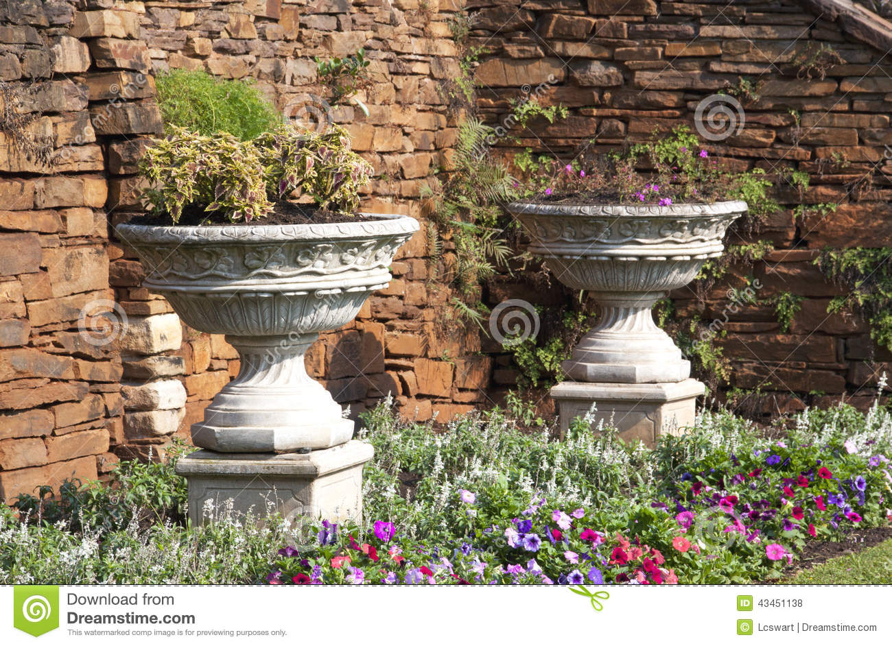 Two Urn Flower Pots In Garden Setting Stock Photo.
