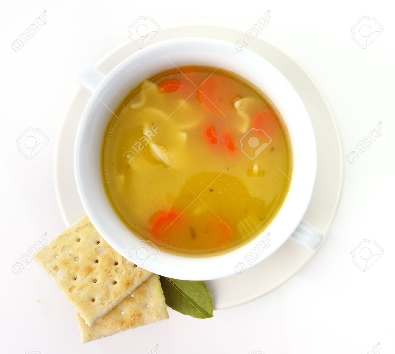 Chicken Noodle Soup In A White Cup With Crackers Stock Photo.