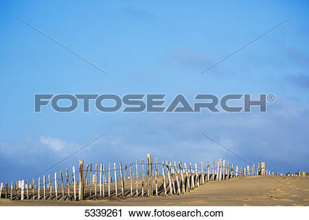 Stock Photography of Wooden post fence along a beach with blue sky.