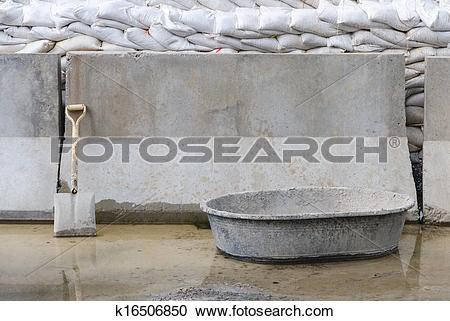 Stock Photography of shovel leaning against wall with concrete.
