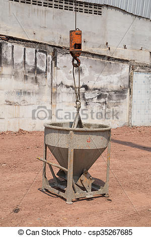 Pictures of Crane lifting concrete mixer container at construction.