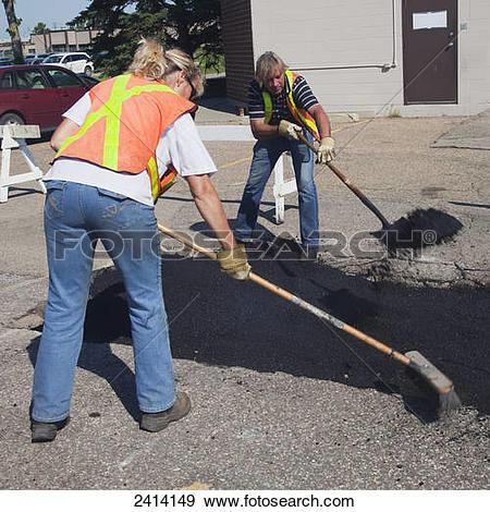 Stock Photograph of Pot hole work crew repairing a parking lot.