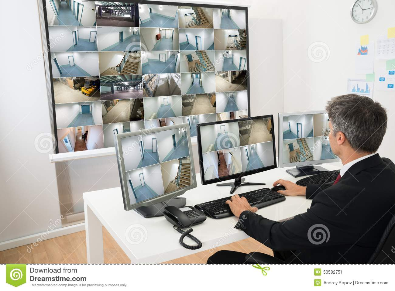 Man In Control Room Monitoring Cctv Footage Stock Photo.