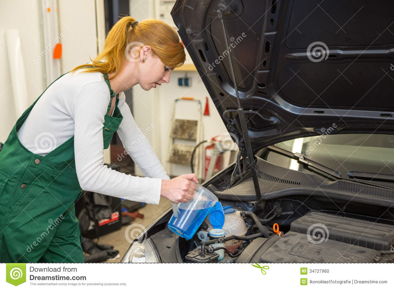 Female Mechanic Fills Coolant Or Cooling Fluid In Motor Of A Car.