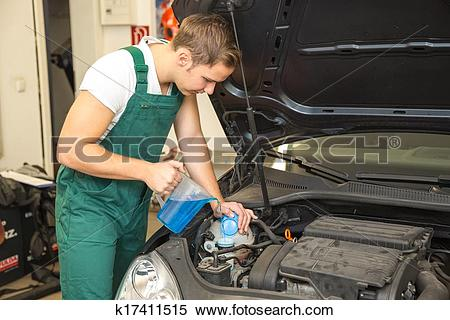 Stock Image of Mechanic fills coolant or cooling fluid in motor of.