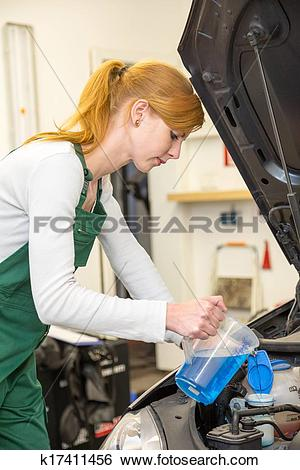 Stock Images of Female mechanic refills coolant or cooling fluid.