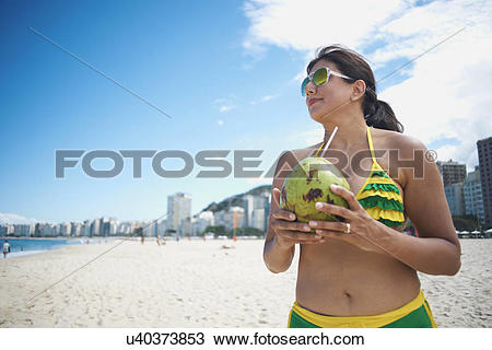 Stock Photo of Mature woman drinking from coconut on Copacabana.