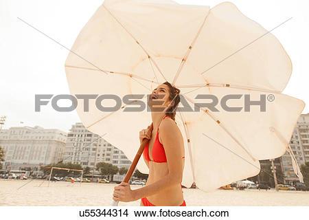 Stock Photo of Woman in red bikini holding beach umbrella.