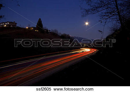 Stock Image of Streaking lights of traffic around a curve under a.