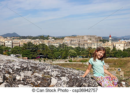 Stock Images of happy little girl sitting on stone wall Corfu town.