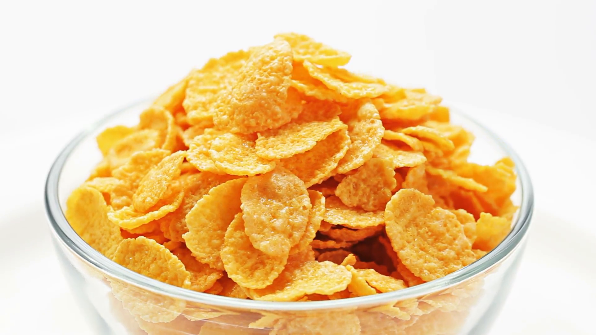 Corn flakes heap in a glass bowl rotating over white, loop ready Stock  Video Footage.
