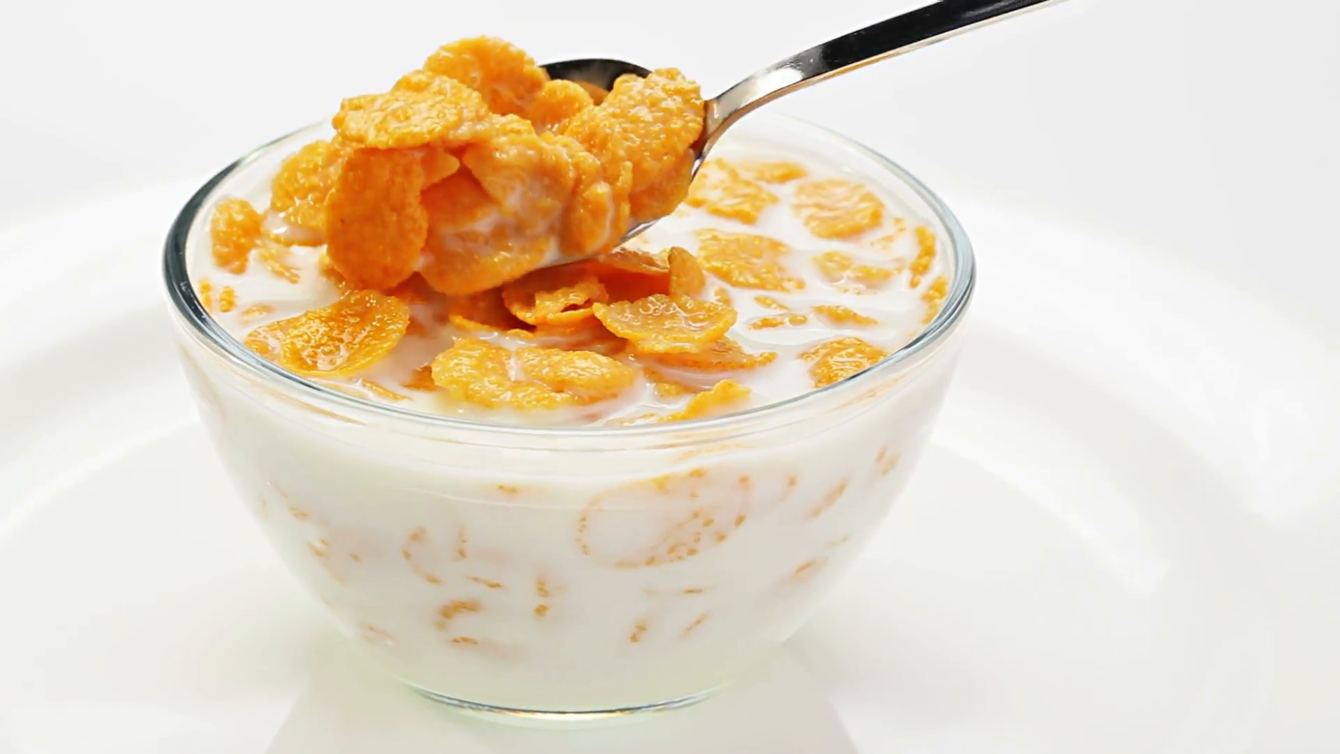 Cooking corn flakes with milk in a glass bowl stirring by spoon over white  Stock Video Footage.