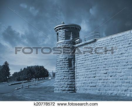 Stock Photo of Guard tower at corner of high prison wall k20778572.