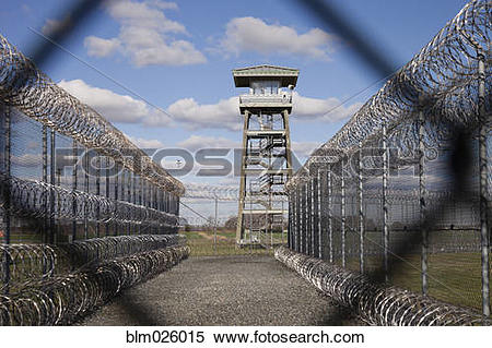 Stock Image of Prison fence, watch tower and barbed wire at.