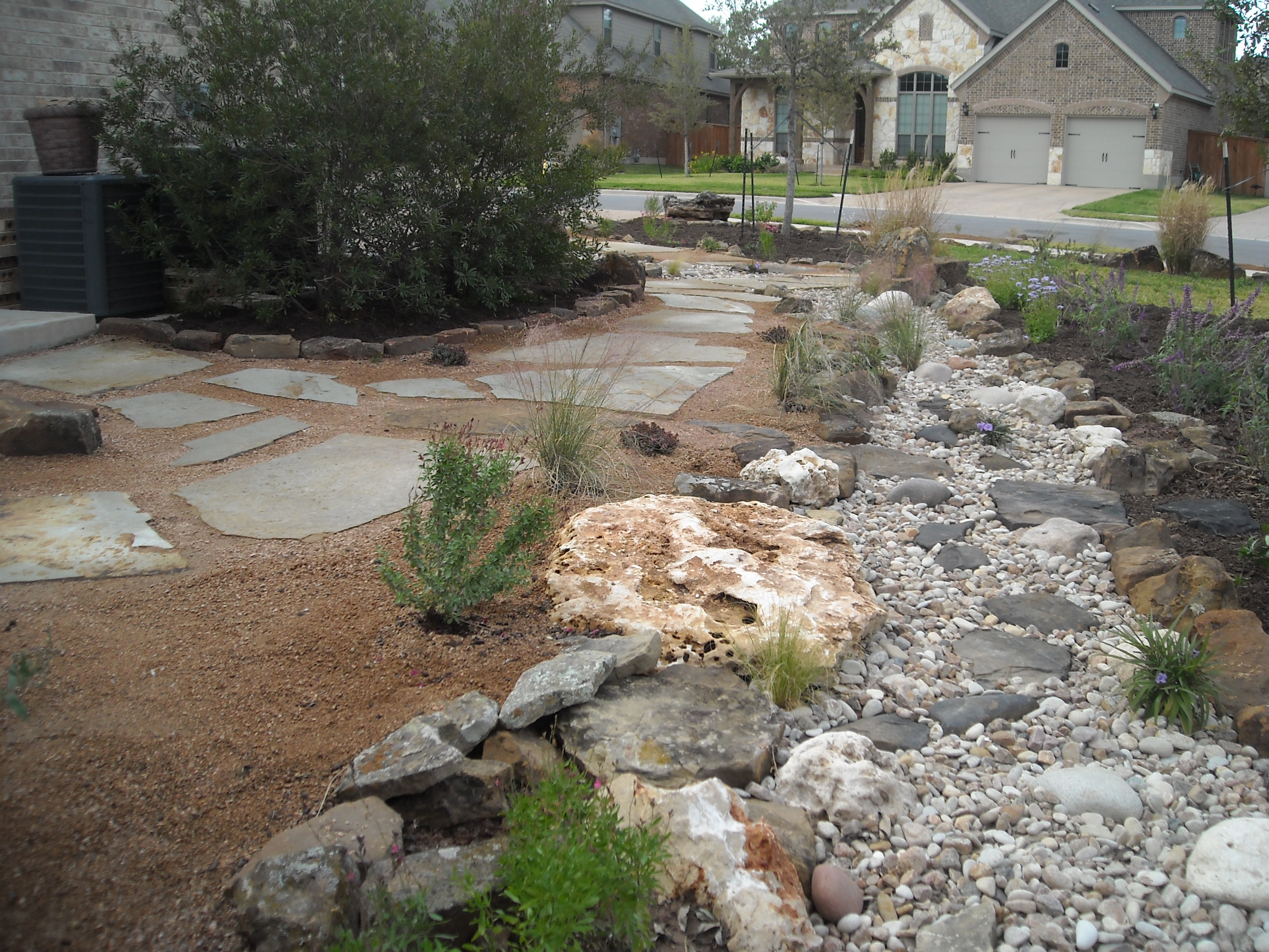 Dry creek bed with decomposed granite beds and flagstone pathway.