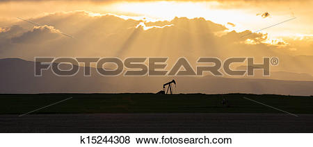 Pictures of Pumpjack with Crepuscular Rays and Rocky Mountains.