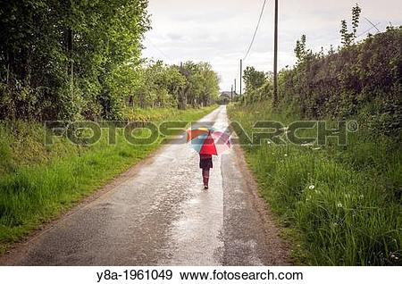 Stock Photograph of A young girl walking in the rain carrying an.