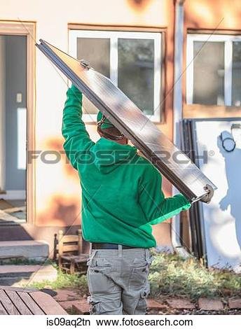 Stock Photo of A construction crew member carrying a solar panel.