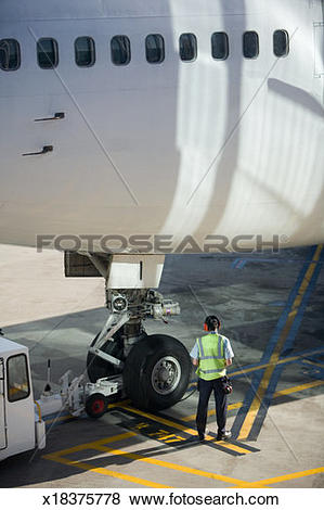 Pictures of Ground crew member working on airplane tire, rear view.