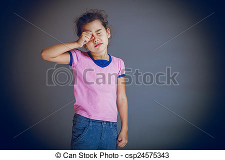 Stock Photo of girl child rubs his eyes on gray background cross.