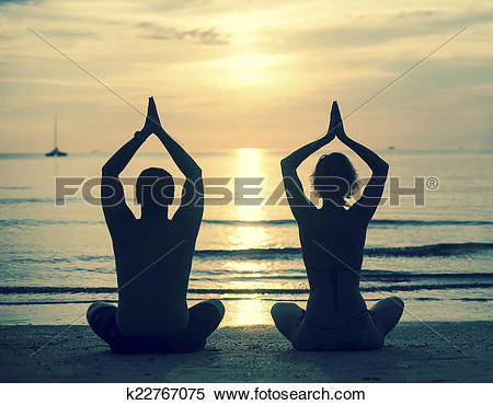 Stock Image of Silhouette of young couple practicing yoga on sea.