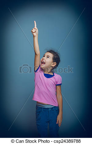 Pictures of teen girl pointing at the sky gray background cross.