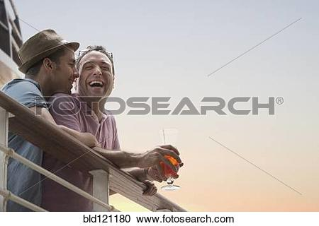 Stock Photography of Gay couple having drinks on cruise ship deck.