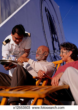 Stock Photo of Serving drinks to mature couple, on deck of cruise.