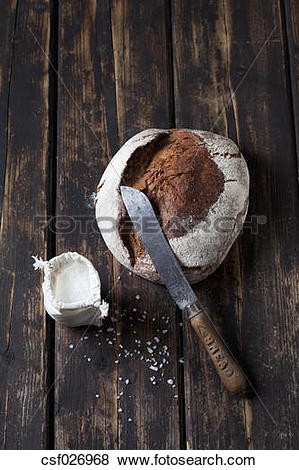 Pictures of Crusty bread, bread knife and sachet of salt grains on.