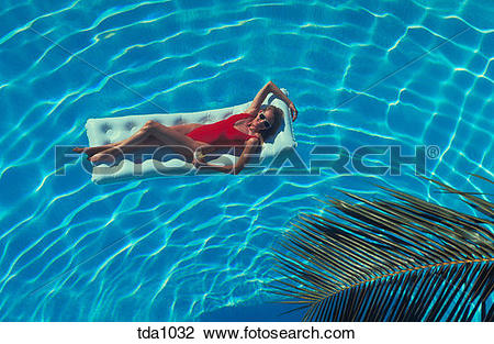 Stock Photo of A young woman in a red bathing suit holding a drink.