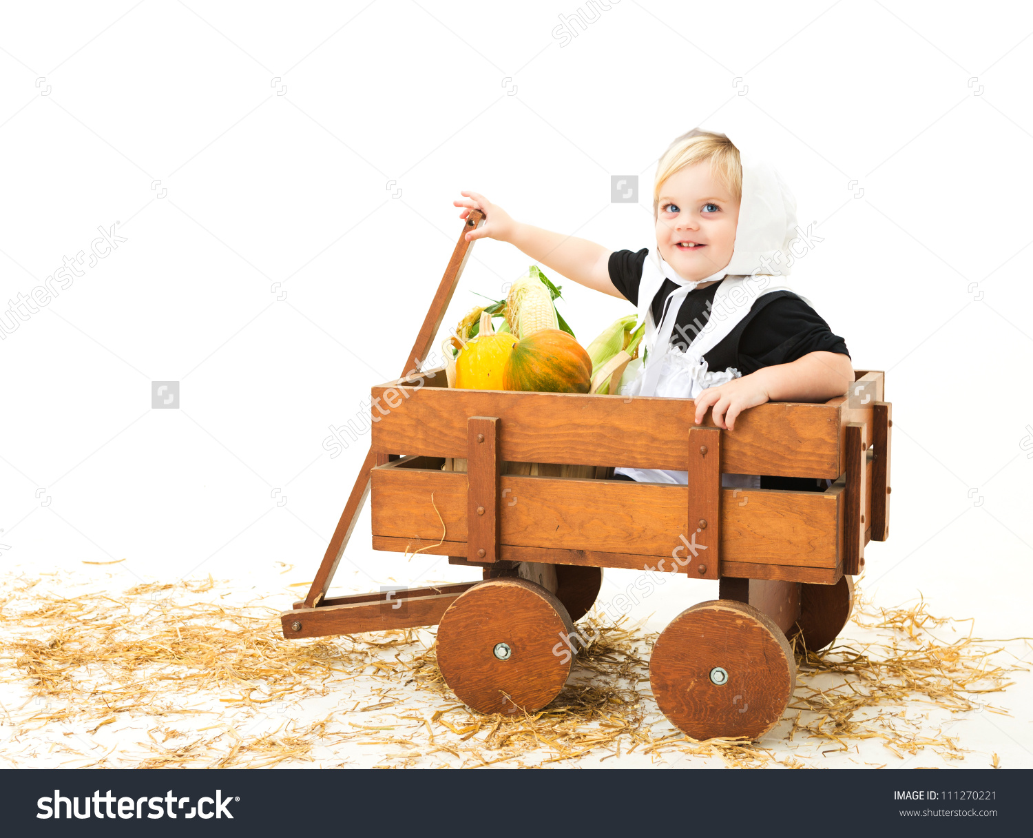 Cute Little Pilgrim Girl In A Wagon Full Of Fall Vegetables Stock.