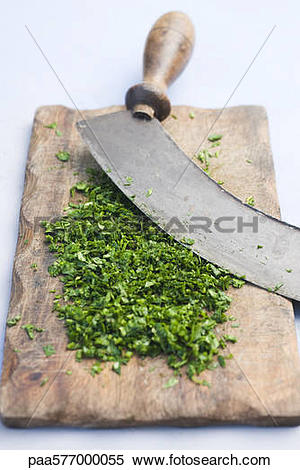 Stock Image of Freshly chopped herbs on cutting board paa577000055.