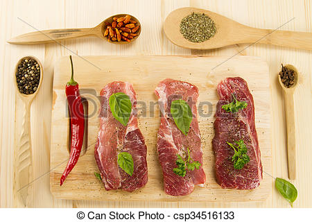 Stock Photos of fresh raw pork on cutting Board with spices and.