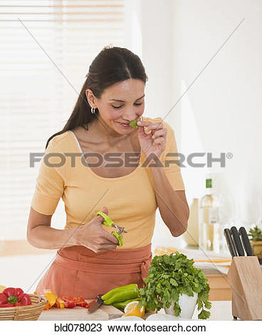 Stock Photo of Hispanic woman cutting herbs bld078023.