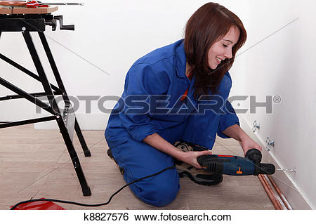 Stock Images of Female labourer drilling hole in wall k8827576.