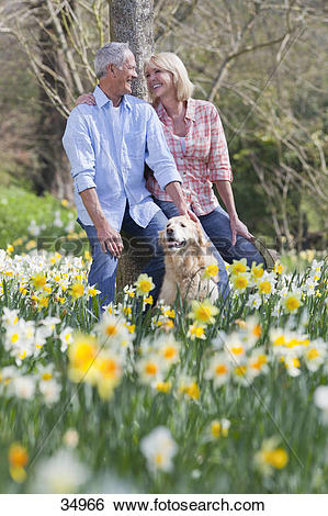 Stock Images of Smiling senior couple with dog leaning against.