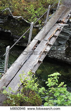 Stock Images of Dangerous old wooden bridge across a river.