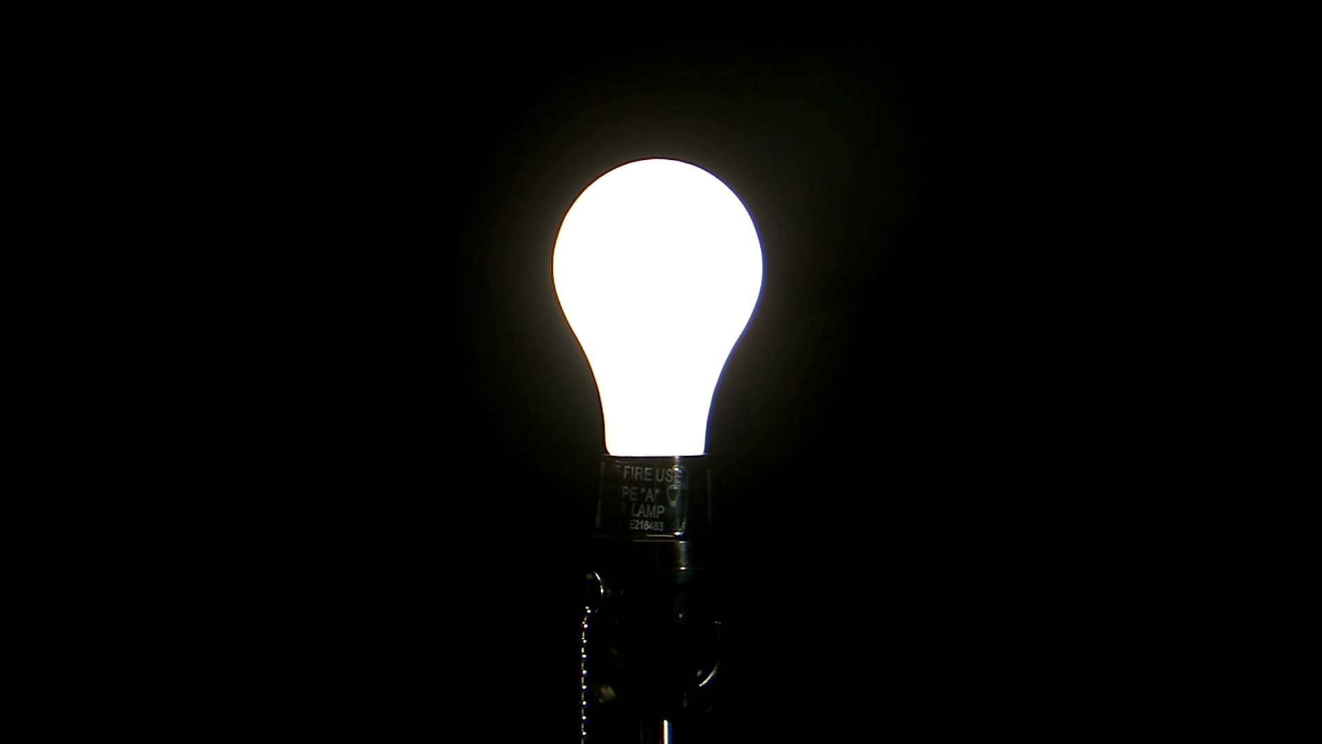 Light Bulb Turning on Against a Black Background, HD Stock Footage.