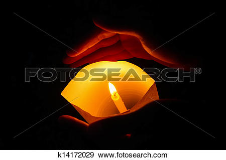 Stock Photograph of Hands holding a burning candle in dark.
