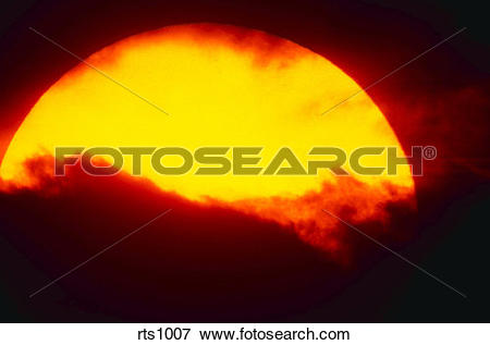 Picture of Large yellow sun against dark sky and clouds at sunset.