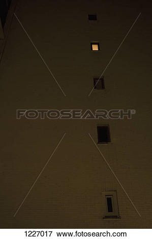 Picture of One illuminated window in an otherwise darkened.
