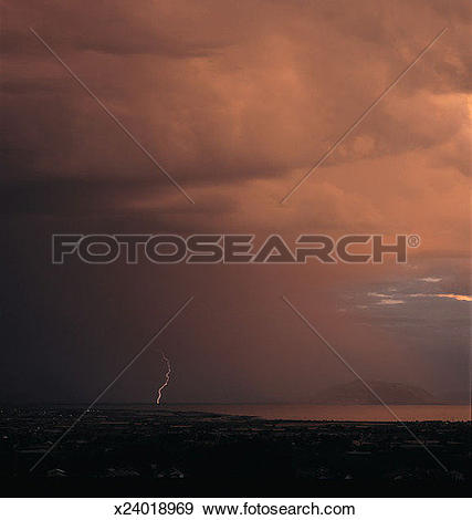 Stock Photograph of a darkly clouded sky releases a lightning bolt.