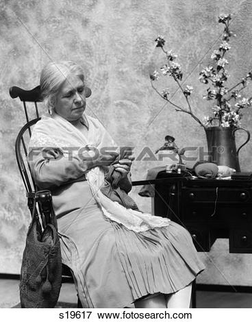 Picture of 1920S Elderly Woman Sitting In Rocking Chair Darning.